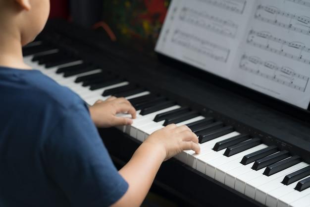 O menino aprende a tocar piano