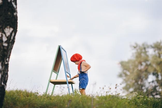O menino artista da natureza desenha uma imagem