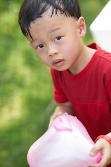 O menino asiático bonito prende o balão dado forma coração cor-de-rosa na terra traseira da parte traseira do jardim da jarda