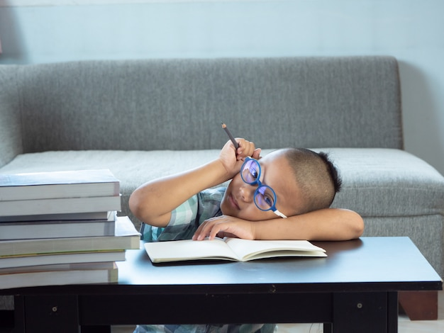 O menino asiático cansado e furado dentro escreve em casa trabalhos de casa. conceito de educação