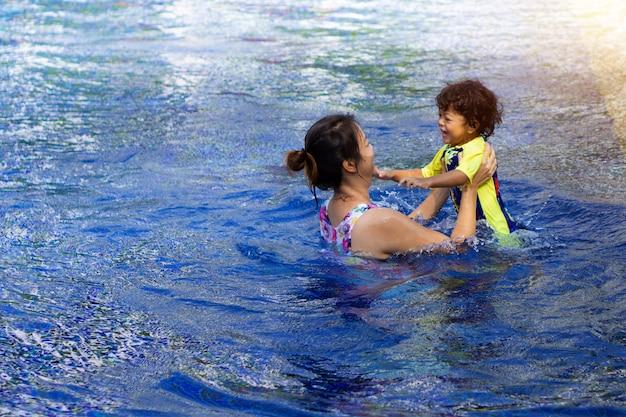 O menino asiático da criança aprende a natação em uma piscina com mamã. - efeito de filtro sunset