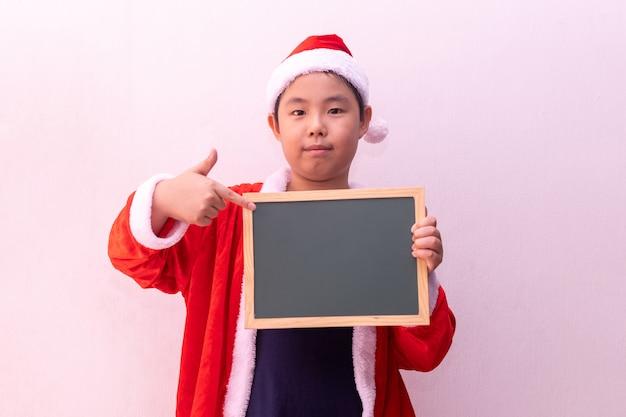 O menino asiático em papai noel veste guardar o tabuleiro vazio. feliz natal