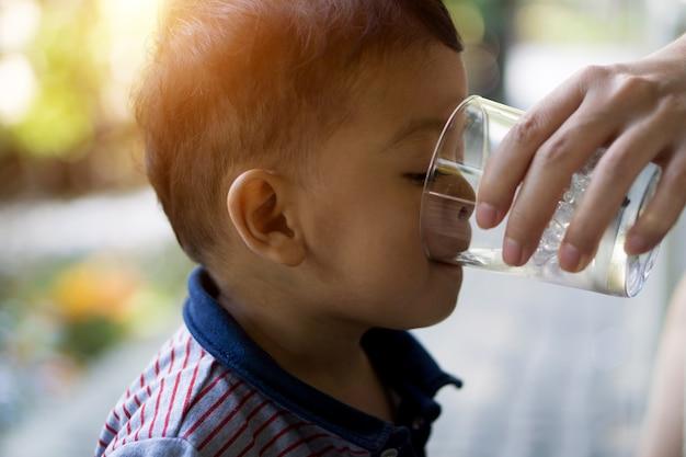 O menino asiático está bebendo a água do vidro claro introduzido por sua mãe.