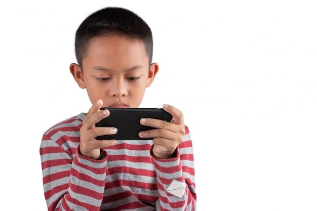O menino asiático está jogando jogos em seu smartphone isolado no fundo branco.