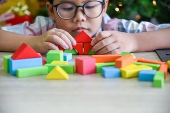O menino asiático está praticando habilidades pela montagem de peças de madeira, geometria.