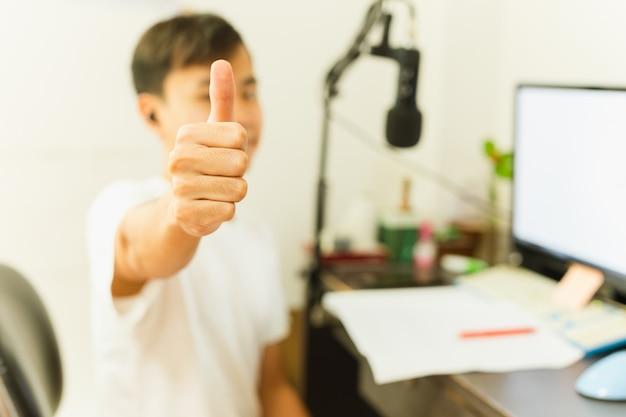 O menino asiático estuda em casa usando o pc e mostrando batidas acima.