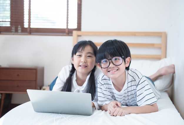 O menino asiático feliz e a menina que jogam o jogo no portátil que encontra-se na cama no quarto na casa, no irmão e na irmã usando o caderno fazem trabalhos de casa, conceito da educação.