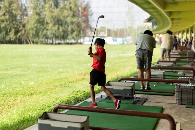 O menino asiático novo está praticando seu balanço do golfe na escala de condução do golfe.