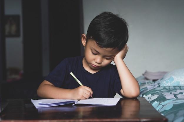 O menino asiático sentado atrás da mesa estava escrevendo algo com preguiça e sem vontade de aprender