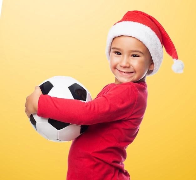 O menino ativo sorrindo com a bola