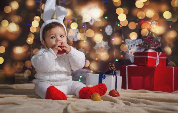 O menino (bebê) na roupa de coelho do ano novo na superfície da guirlanda de natal e caixas de presente com fita.