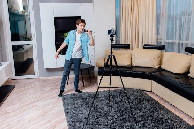 O menino blogueiro está transmitindo ao vivo. o adolescente está cantando ao microfone.