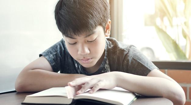 O menino bonito asiático leu livros no café.