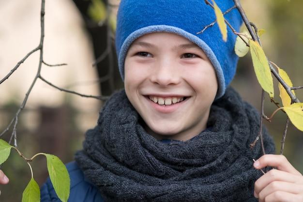 O menino bonito da criança que veste o inverno morno veste guardar o ramo de árvore com as folhas verdes no tempo frio ao ar livre.