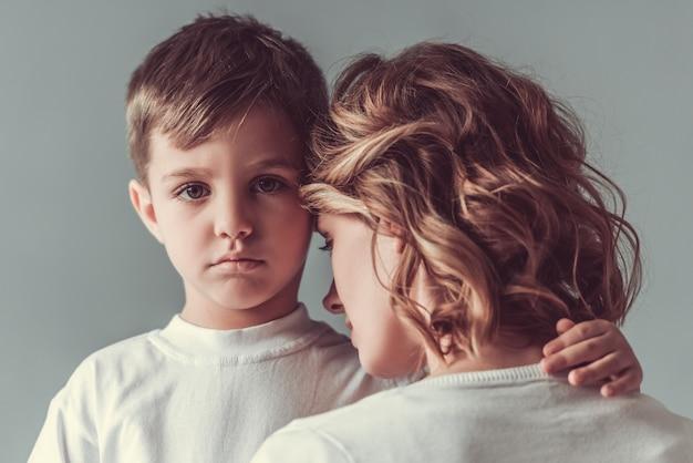 O menino bonito está abraçando sua mãe e olhando tristemente na câmera.