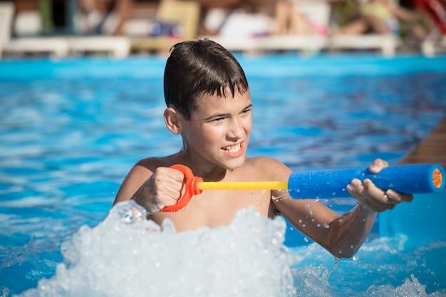 O menino brinca na piscina com uma pistola de água