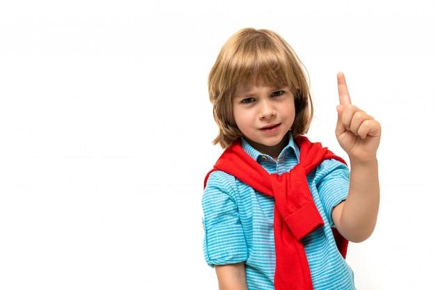 O menino caucasiano senta-se em uma cadeira com sweatshot vermelho em volta do pescoço aponta um dedo isolado no fundo branco
