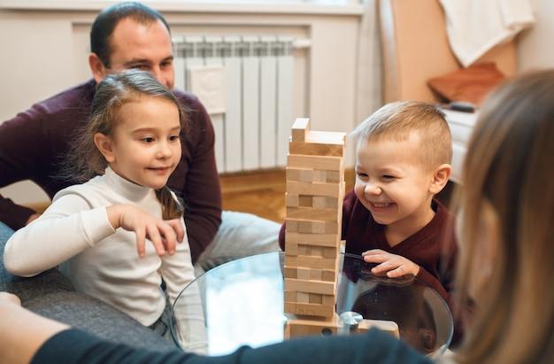 O menino caucasiano sorridente está jogando jenga com a irmã mais velha, enquanto os pais olham com orgulho