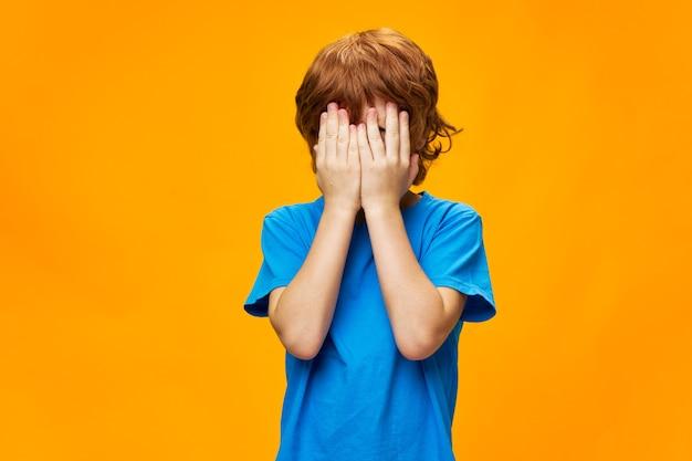O menino cobriu o rosto com as mãos cabelo vermelho rasga camiseta azul