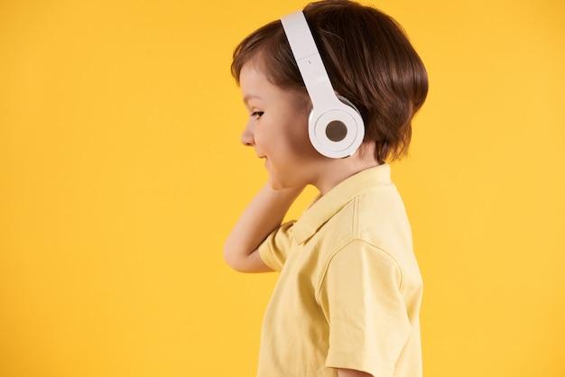 O menino com auscultadores escuta a opinião lateral da música.