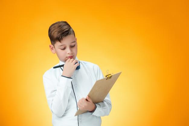 O menino com caneta e tablet para anotações