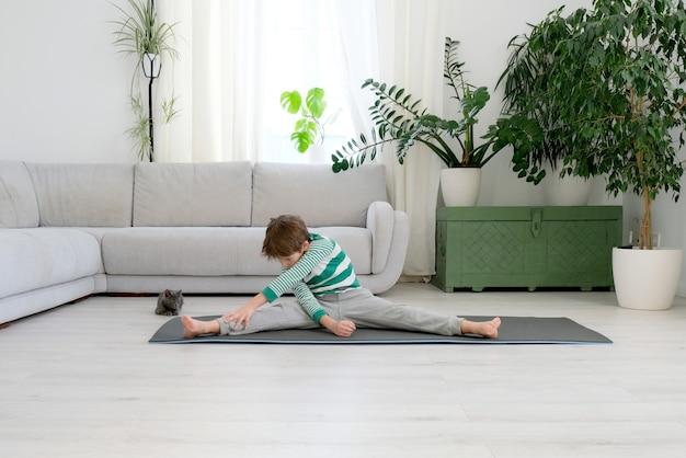 O menino com o animal de estimação pratica esportes em casa online. a criança faz exercícios na sala.