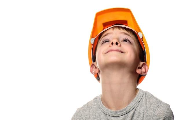 O menino com o capacete de construção laranja levantou a cabeça. retrato, rosto. isole em fundo branco.
