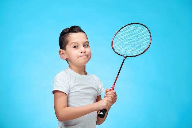 O menino com raquetes de badminton ao ar livre