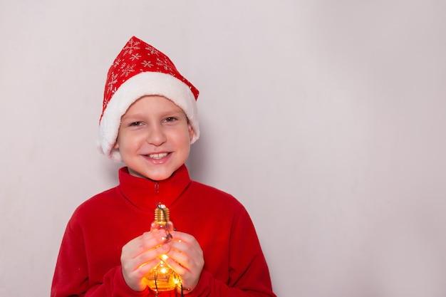 O menino com um chapéu de ano novo com uma lâmpada mágica