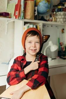 O menino com um chapéu vermelho e uma camisa xadrez joga a balalaica. rapaz bonito segurando seu violão. aulas de música em casa. hobby para a alma. música para ensino familiar