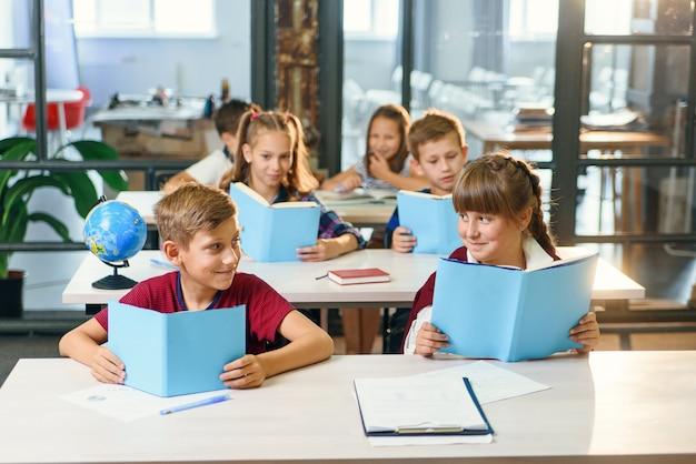 O menino considerável e a menina bonita da escola que sentam-se junto na mesa, olham-se e sorriem-se ao ler o livro na lição.