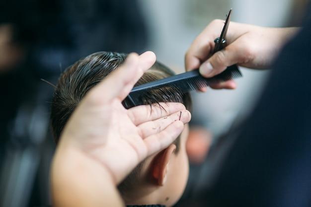 O menino cortando cabelo com tesoura na barbearia