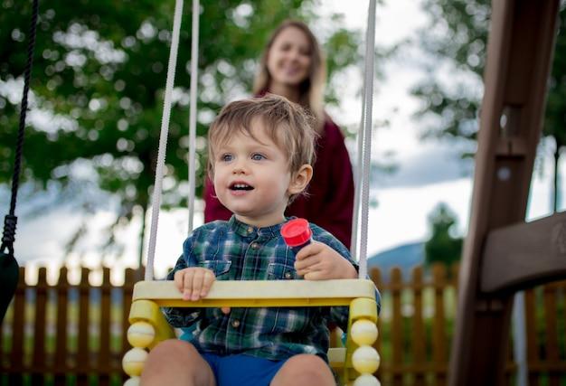 O menino da criança é passeio em um balanço com uma mãe