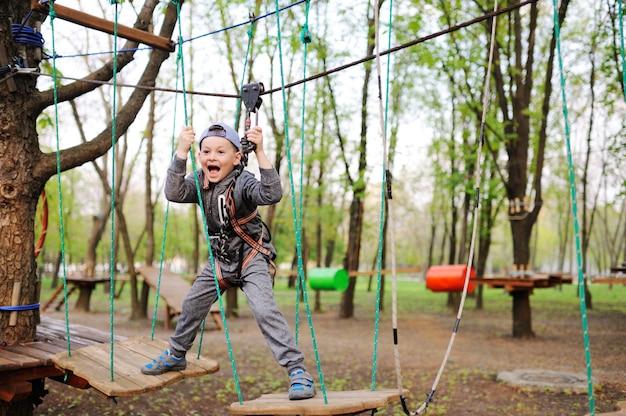 O menino da criança em idade pré-escolar é um obstáculo em um curso alto da corda do equipamento do alpinism da segurança