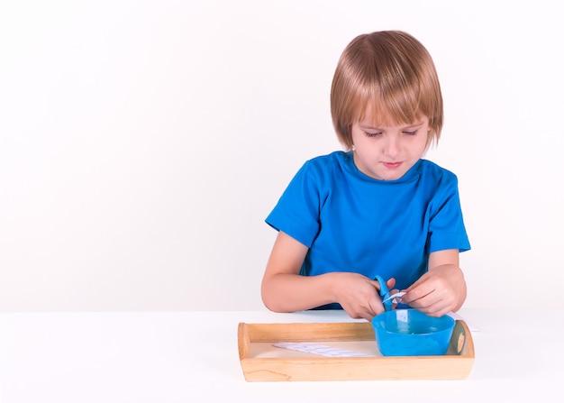 O menino da criança senta-se pela tabela com uma bandeja de materiais de montessori para uma lição da vida prática em um fundo branco