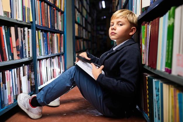 O menino da escola gosta de obter novas informações dos livros, ele se senta na biblioteca à noite depois da escola, no chão