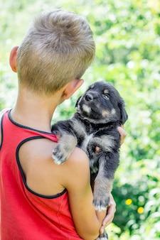 O menino de camisa vermelha segura um cachorrinho preto nas mãos