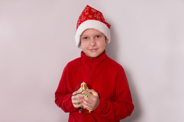 O menino de chapéu de ano novo com uma lâmpada mágica