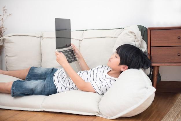 O menino de escola asiático pequeno na camisa branca que coloca em sua cama joga no portátil. conceito de dependência de rede social. dependência do pc filho