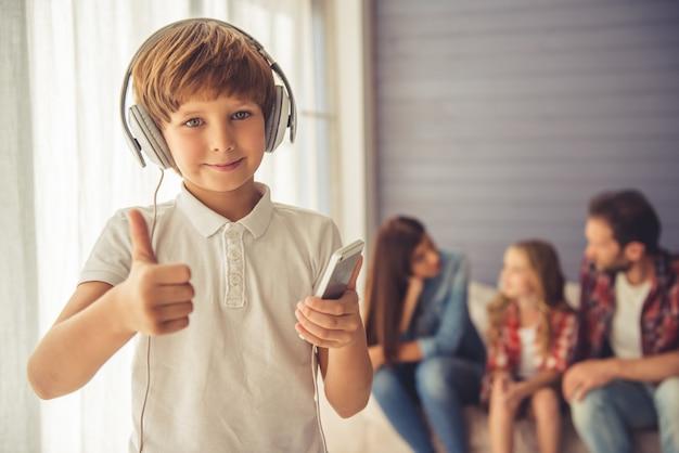 O menino de escola bonito nos auscultadores está escutando a música.