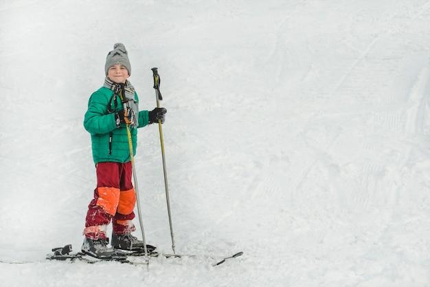 O menino de esquis com bastões de esqui sorri.