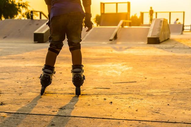 O menino de patins no parque público com equipamentos de proteção no fundo por do sol