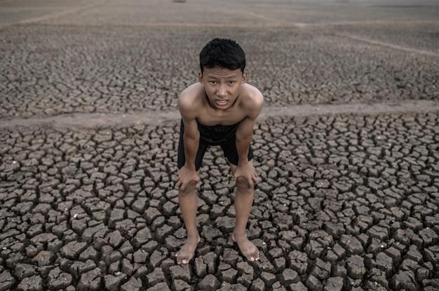 O menino de pé curvado e mão pega joelhos, aquecimento global e crise da água