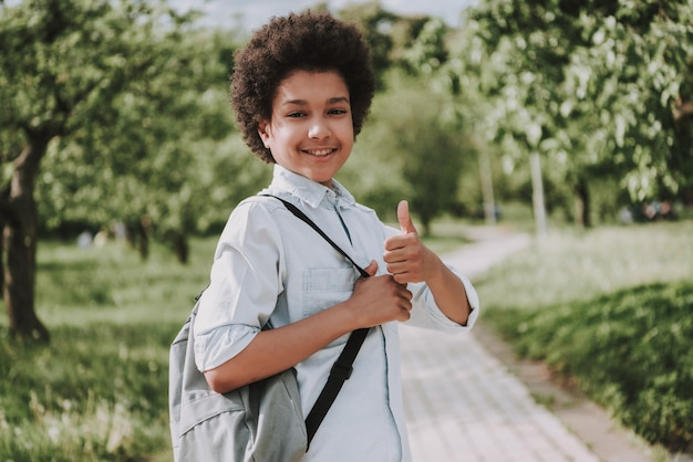O menino de sorriso com trouxa mostra os polegares acima no parque.