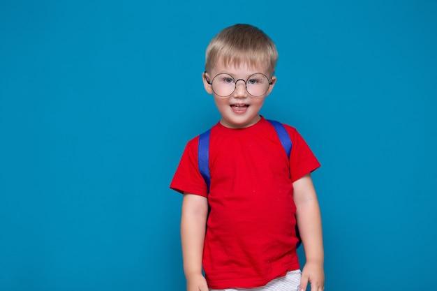 O menino de sorriso feliz no t-shirt vermelho em vidros redondos está indo à escola pela primeira vez. criança com bolsa escola. garoto de volta à escola