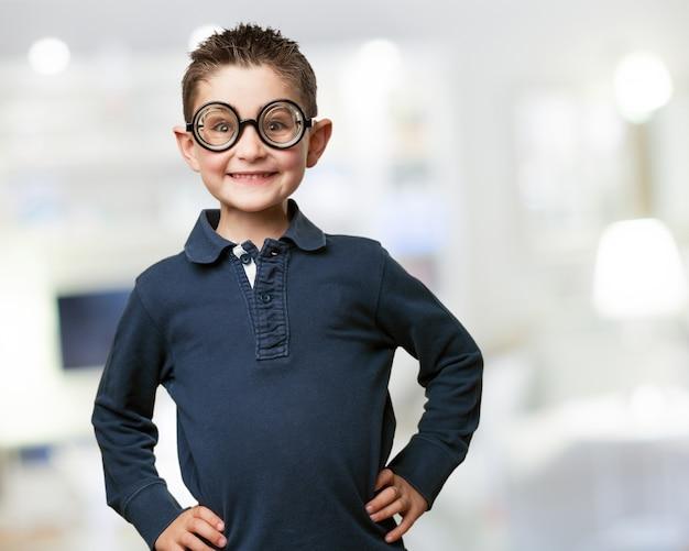 O menino de sorriso que levanta com falsos óculos