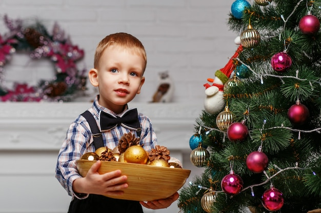 O menino decora uma árvore de natal no interior com enfeites de natal