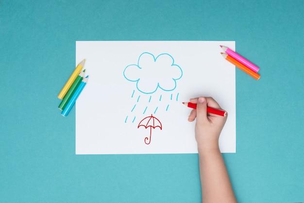 O menino desenha em uma folha de papel branca