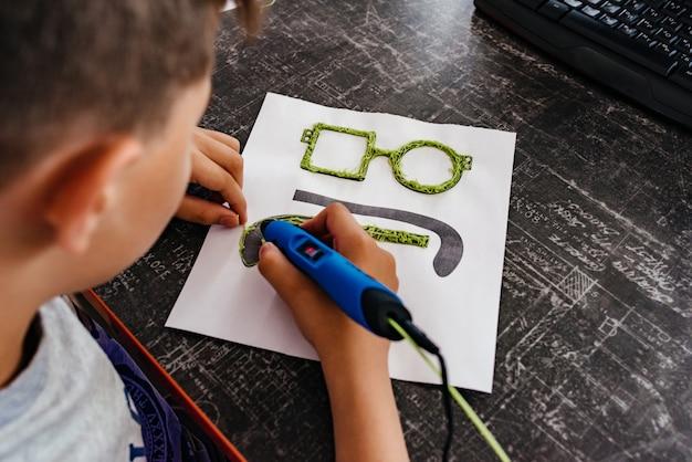 O menino desenha o punho de óculos 3d