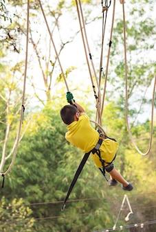 O menino do asean nodos a corda e sorrindo felizmente na árvore obscura do fundo da aventura do acampamento.